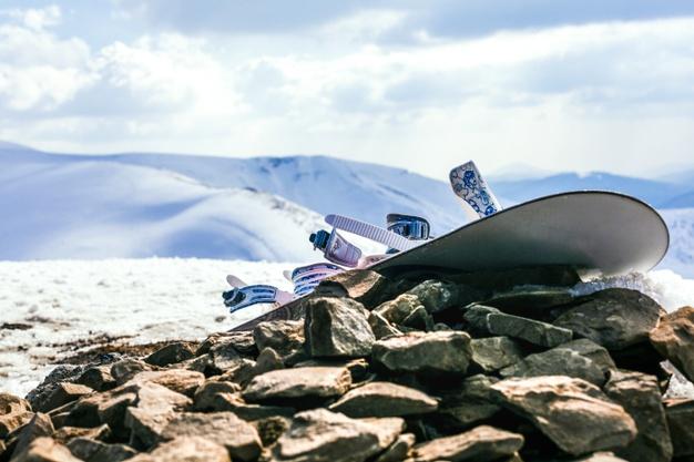 snowboard-with-bindings-rocks-snowy-mountain-landscape_23-2148153655